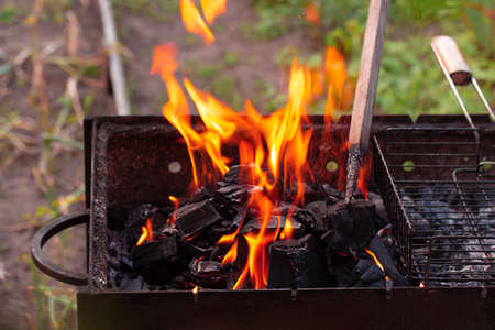 Fire on the empty grill. Cooking at the backyard. Summer bbq party Standard-Bild