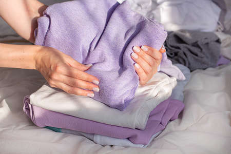 Feminine hands getting clothes into the shape of a small rectangle. Neatly folded clothes