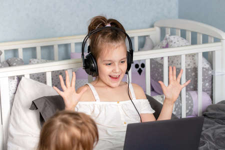 Happy girl learning online with laptop at living room. New normal. Cute happy little girl with smile Banque d'images