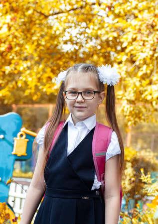 Smart little girl in blue school uniform. Back to school concept. Vertical image