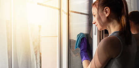 Young woman washing window in home. General cleaning concept