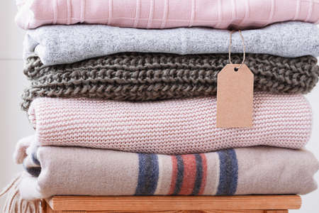 Pile of stacked warm sweaters in pastel colors with craft label.
