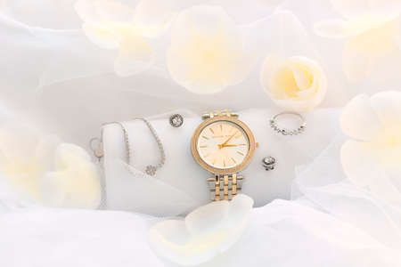 Airy composition with wristwatch, flower petals and jewerly above white background. Spring set accessories for trendy look