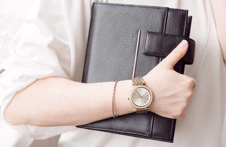 Young business woman wear wrist watch with crystals and holding leather black day planner. Stay focused concept. Stock fotó