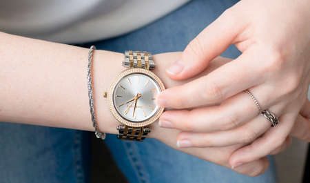 Young woman wearing blue jeans and analog wrist watch with crystal. Stylish girl checking time on her gold and silver luxury watch.