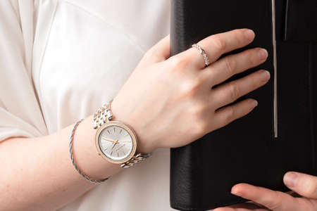 Young business woman wear silver and golden wrist watch and holding leather black day planner. Being in control concept.