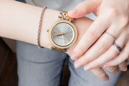 Silver and golden analog wrist watch on feminine hand. Young woman checking time. Silver jewelry set on female hands. Stock fotó