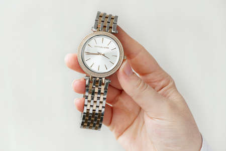 Human hand holding wristtwatch with metal bracelet shooted above white background. Close up image. Elegant accessories
