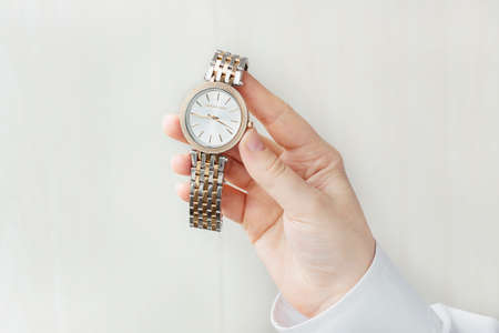 Human hand holding wristwatch with metal bracelet shooted above white background. Elegant accessories for luxury look.