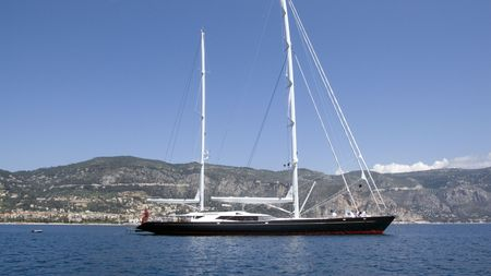ketch: Black streamlined two mast modern sailing yacht anchored in a bay in France Stock Photo