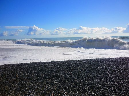 pounding: heavy waves pounding the stone beach in the Mediterranean in Italy exploding into foam
