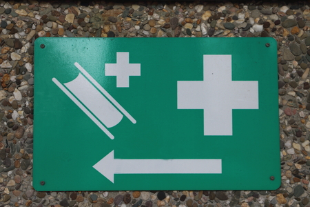 safety sign on the wall pointing to the medical kit and stretcher