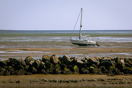 The Wadden Sea, with its fascinating interplay of high and low tide or in other words ebb and flow, gives you a great view on the soil of the sea, the boats are waiting for the new flow to sail again, picture tasks at Schiermonnikoog