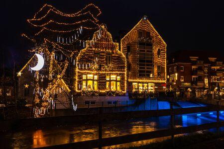 Wieczorny jarmark bożonarodzeniowy z mnóstwem żółtych lampek choinkowych na budynkach w mieście Nordhorn kraj Niemcy