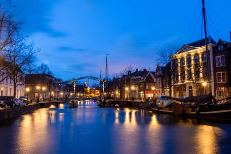 The center of Schiedam with beautiful narrow streets and small canals, photo tasks in the evening hours with beautiful orange and blue clouds. South Holland Province Reklamní fotografie