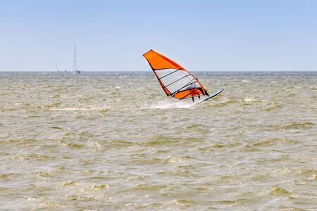 A lonely windsurfer in a strong wind on the IJsselmeer in the Netherlands, province Friesland