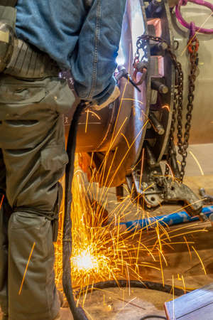 A welder grinding and welding on a metal pipe piece for industrial use
