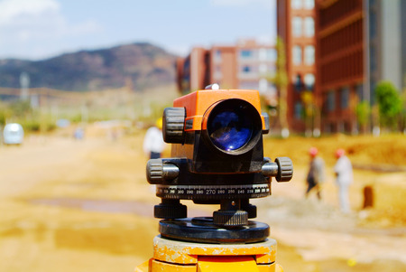 manual measuring instrument: Land surveyors working on a construction site with their total station Stock Photo