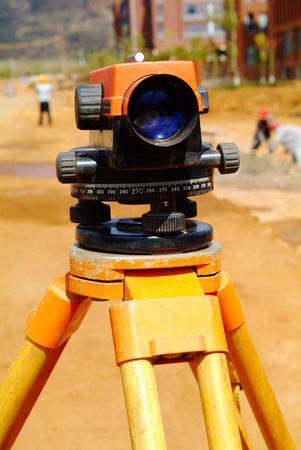 electronic survey: Surveying measuring equipment theodolite transit on tripod at construction building area site.