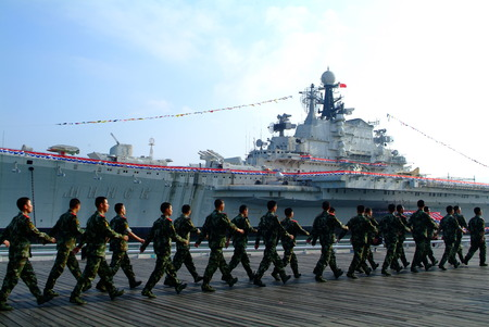 Warship in the bay and chinese Soldier training. 報道画像