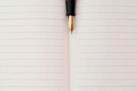 diagonal diary education: Closeup photo of notebook with old golden ink pen Stock Photo