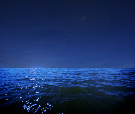 This photo illustration of a deep blue moonlit ocean at night with calm waves would make a great travel background for any coastal region or vacation.