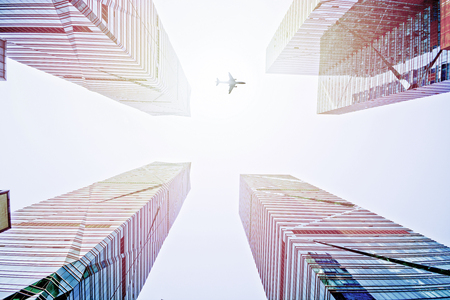 Low angle view of plane flying pass a city