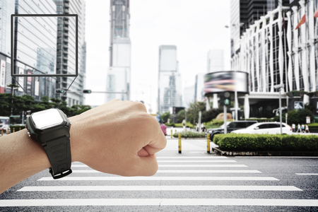 Person holding up wrist watch in a city 版權商用圖片