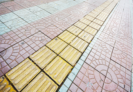 Tactile paving for blind handicap on tiles pathway.