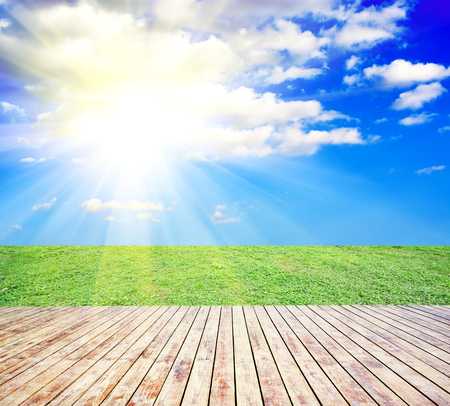 木板地板與綠草和藍天作為背景