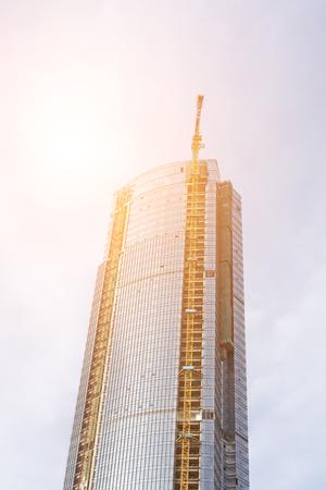 tower crane on top of construction skyscraper building over blue sky. 新聞圖片