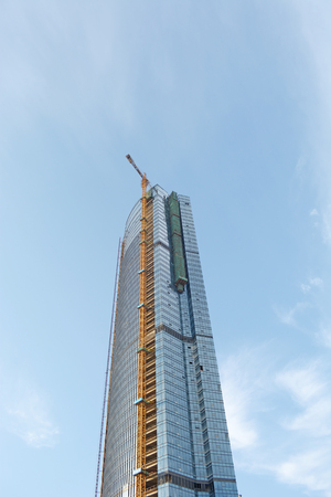 tower crane on top of construction skyscraper building over blue sky. 新聞圖片