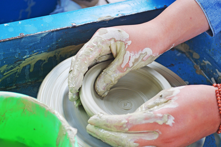 Hands of a woman creating a clay jar on a potters wheel