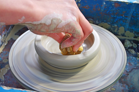 potters wheel: Hands of a woman creating a clay jar on a potters wheel