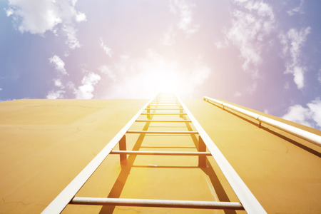 Ladder over the brown wall into sky Stock Photo