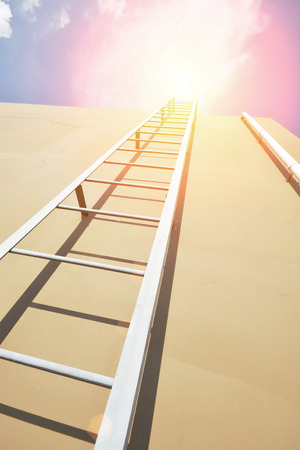 rungs: Ladder over the brown wall into sky Stock Photo