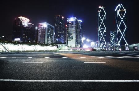 Empty asphalt road and modern skyline at night