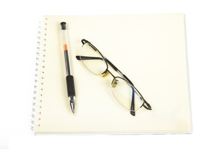 glasses with pen on notebook photo