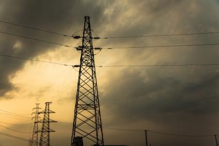 electric pylon under sunset sky with orange color photo