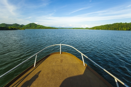 ship deck with railing aiming to an island in a lake photo