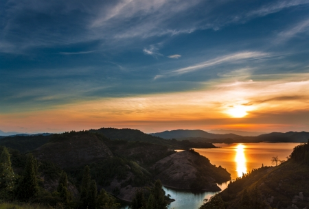 coucher de soleil sur un lac avec des montagnes