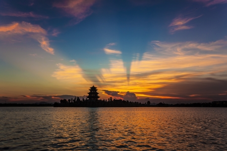 chinese ancient tower pavilion under sunset with colorful sky and clouds photo