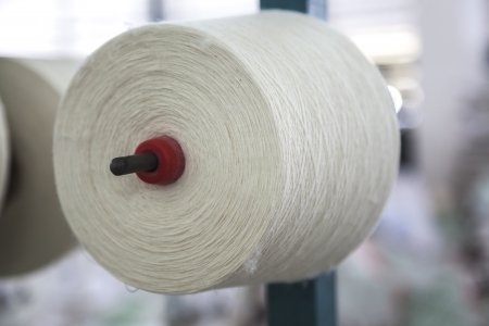 cotton reel stacked in a big rack for weaving in a cloth factory photo