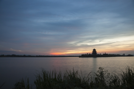 sunset in a lake with chinese ancient tower building  photo