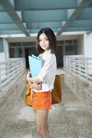 asian female standing in the campus with file folder in her hand photo