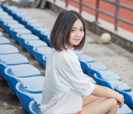 siting: asian female siting in the campus stadium with casual clothes