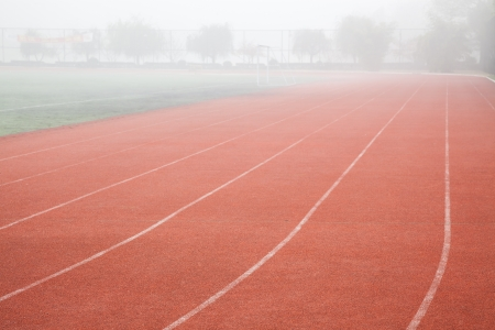 red track lane with white lines in the running sports field Stock Photo - 17844306
