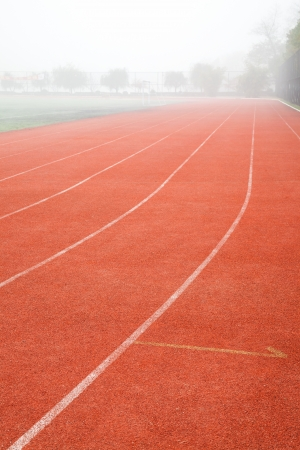 red track lane with white lines in the running sports field Stock Photo - 17844324