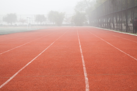 red track lane with white lines in the running sports field Stock Photo - 17844287