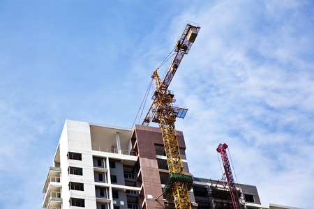 An unfinished apartment with crane working.
